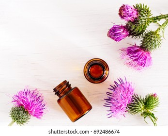 burdock oil in small glass bottle and burdock flowers on white wooden table. Top view or flat lay. Copy space.
