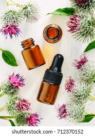 burdock oil in small glass bottle with pipette and burdock flowers on white wooden table. Top view or flat lay. Vertical.