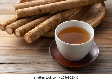 Burdock tea placed against a background of wooden boards. A raw burdock behind it