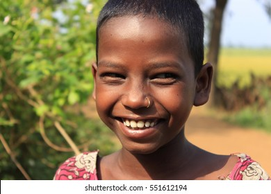 Burdwan, West Bengal, India on 7th May in 2014 - Homeless kid. Portrait of a little Indian kid. Portrait of a poor little smiling girl.