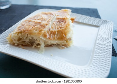 Burek (traditional balkan food) with cheese on a plate in small bakery