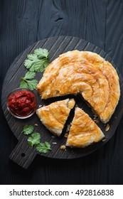Burekas pie stuffed with meat, black wooden surface, top view