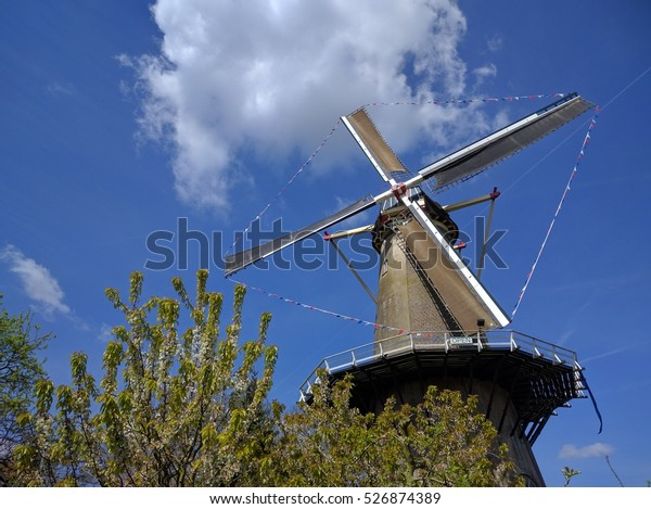 BUREN, THE NETHERLANDS - MAY 5, 2016: Tower mill Prins van Oranje (The Prince of Orange) in Buren, The Netherlands, decorated with flags for the occasion of a Dutch national holiday.
