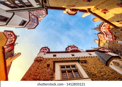 Burg Eltz, the famous medieval castle in Germany, low angle view from the courtyard up to the colorful half-timbered towers on sunset