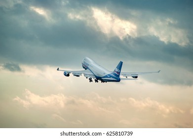 Burgas airport, Bulgaria - April 19, 2015: American wide-body commercial jet airliner and cargo aircraft Boeing 747 Jumbo Jet of Silk Way Airlines takes off against unique dramatic cloudy sky.