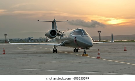 Burgas airport, Bulgaria - May 22, 2015: Airplane on the apron against beautiful sunset. Learjet 60 is a mid-size cabin, medium-range business jet aircraft manufactured by Bombardier Aerospace, USA.