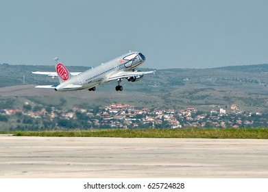 Burgas airport, Bulgaria - Sept 7, 2014: Airplane Airbus A320 is taking off against beautiful landscape with village houses on the hills near the runway. Niki is an Austrian low-cost airline.