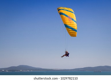 Burgas - August 12: Orange with blue paraglider flying against the blue sky and sea on August 12, 2017, Burgas, Bulgaria