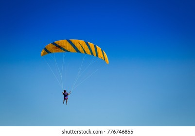 Burgas - August 12: Orange with blue paraglider   flying against the blue sky on August 12, 2017, Burgas, Bulgaria