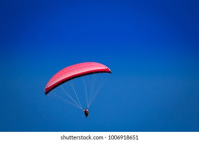 Burgas - August 12: Red tandem  paraglider flying against the blue sky on August 12, 2017, Burgas, Bulgaria