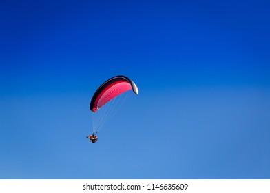 Burgas - August 12: Red tandem paraglider flies against blue sky on August 12, 2017, Burgas, Bulgaria