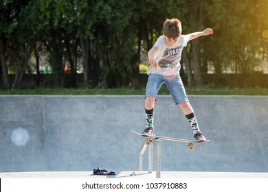 Burgas, Bulgaria - 6.7.2016: Young kid balancing his skateboard on a steel ramp in the local city skate park on a sunny summer day.