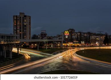 BURGAS, BULGARIA - FEBRUARY 1, 2018: Overhead pedestrian bridge at night. McDonald's restaurant logo.