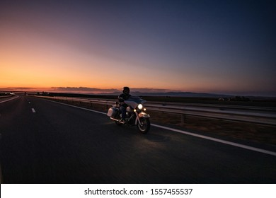 Burgas, Bulgaria - September 30.2019 Motorcyclists on а Honda Shadow driving on the asphalt road in rural landscape at sunset with dramatic clouds.