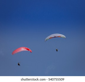 Burgas - July 29: Two paraglider - red and multicolored flying against the blue sky on July 29, 2016, Burgas, Bulgaria