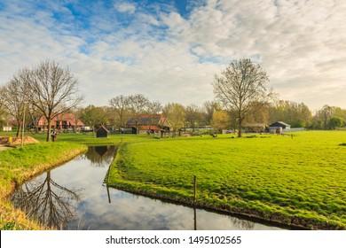 """Burgemeester Bruins Slotsingel, Alphen aan den Rijn, Zuid Holland, Netherlands, April 12, 2019: Zegersloot petting farm and """"de Schaapskooi"""" pancake farm against blue skies with clouds"""