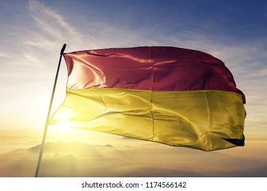 Burgenland state of Austria flag textile cloth fabric waving on the top sunrise mist fog