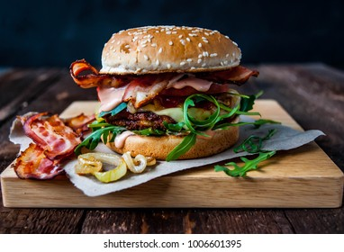 Burger with bacon and fried onions on a wooden board. Dark, wooden background.