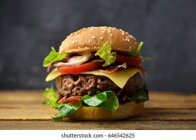 Burger with bacon on wooden table