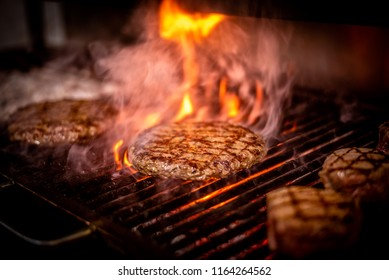 Burger barbeque being cooked on hot firey streamy flame.