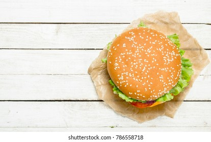Burger with beef, cheese and vegetables on paper. On a white wooden background.