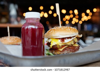 Burger and berry drink on restaurant table, high calorie junk food