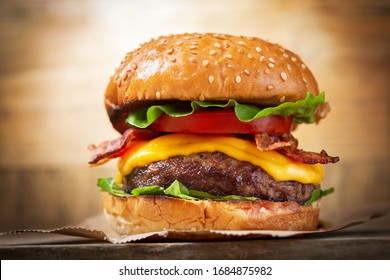 burger with cheese, bacon, salad and vegetables on a wooden  board