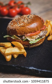 Burger with cheese and french fries or chips on darj stine table