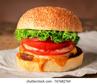 burger with cheese on piece of paper on wooden background