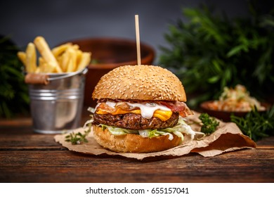 Burger with cheese, salad and fries potato on wooden background