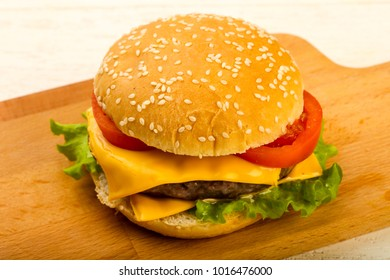 Burger with cheese, tomato and salad leaves