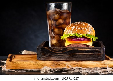 Burger cheeseburger with cutlet, cheese and vegetables in a wooden lunch box and a drink with ice