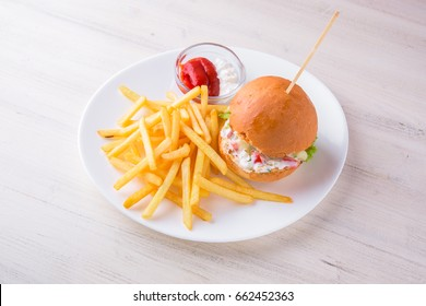 Burger with chicken, French fries and sauce. Children's menu in the restaurant. A healthy, nutritious, balanced diet for children.