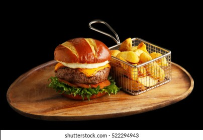 burger and chips on a plate isolated on black background