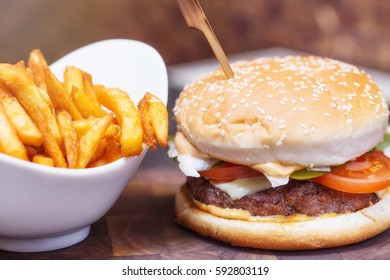 Burger close up with fresh tomato, cheese, meat and french fries.