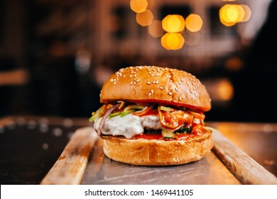Burger with cutlet of marbled beef, mozzarella, onion, chili pepper, eggplant, with spicy tomato sauce on a white bun with sesame seeds served on a wooden board