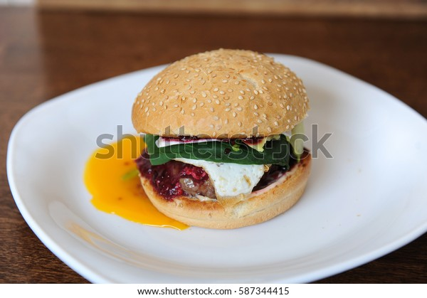Burger with cutlet, vegetables, cheese and berry sauce closeup on a white plate on a wooden background. Egg yolk leaked