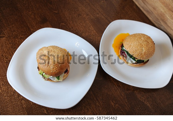 Burger with cutlet, vegetables, cheese and berry sauce closeup on a white plate on a wooden background. Egg yolk leaked. Top view