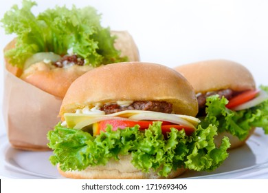 Burger is delicious American fast food. Closeup group of set three hamburger made from pork or beef, green lettuce bread onion and tomato in a paper bag and dishes on a white table background at home