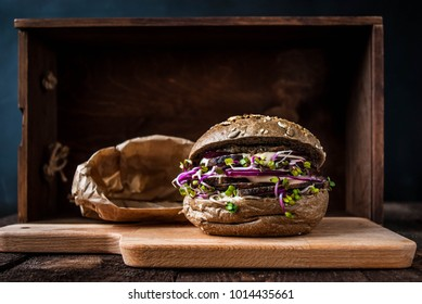 Burger with duck meat, radish sprouts and red onions served on a wooden board in peper bag. Brown wooden table.