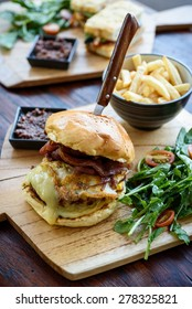 Burger with egg, cheese and bacon, served with salad, fries and relish.