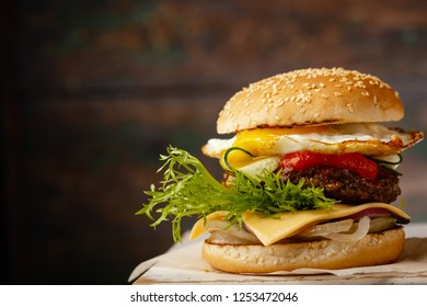 Burger with eggs on  dark wooden background