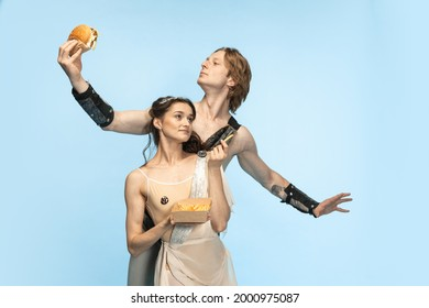 Burger and fast food. Young couple of ballet dancers in ancient Rome costums at blue studio. Historical character, creative, classical art, comparison of eras concept. Beautiful male, female perfomers