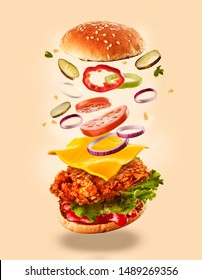 Burger with flying ingredients. Delicious monster Hamburger cheeseburger explosion concept flying ingredients.