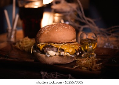 Burger food photo. Street food. Fresh tasty grilled beef hamburger cooked at barbecue on wooden table. Big cheeseburger with steak meat closeup with unfocused background. Rustic color style.