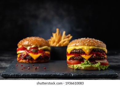Burger with french fries on a dark background