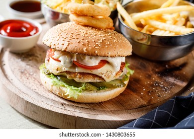 burger and French fries on wooden plate