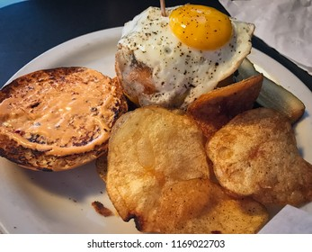 Burger with fried egg and potato chips. Close up