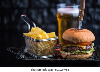 Burger, fried potatoes and beer on a dark background close-up. Street food. Fast food.