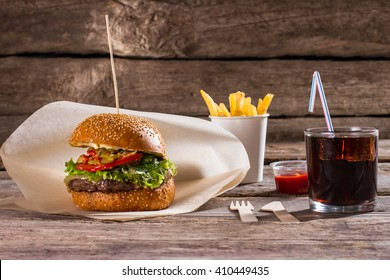 Burger with fries and cola. Beverage and hamburger on stick. Delicious fast food with drink. New dishes worth tasting.